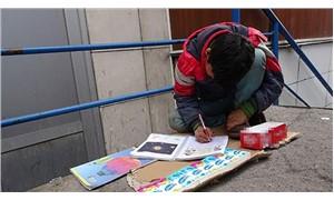 Okul çıkışı sokakta mendil satarken ders çalışıyor